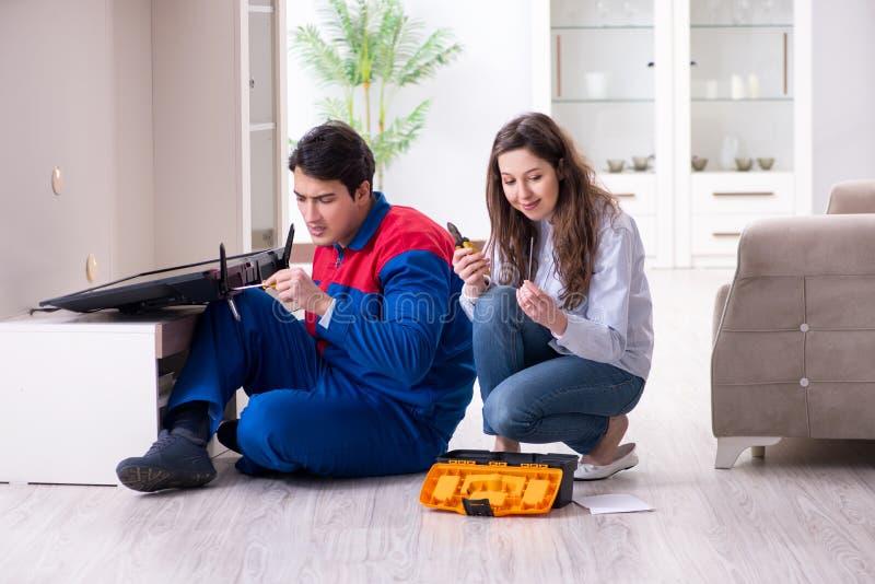 The tv repairman technician repairing tv at home royalty free stock image