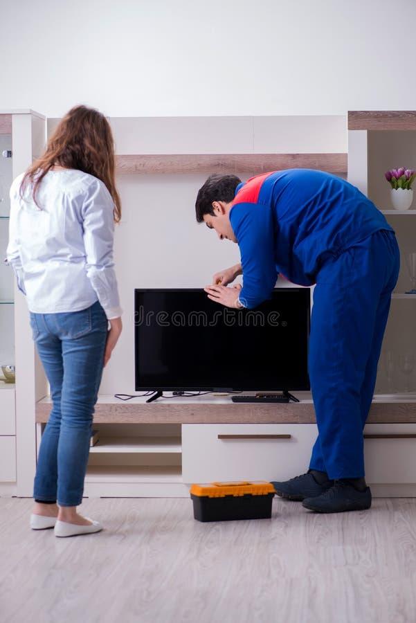 The tv repairman technician repairing tv at home royalty free stock photography