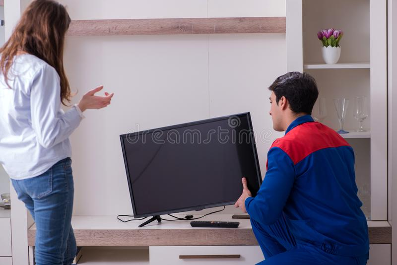 The tv repairman technician repairing tv at home stock photography