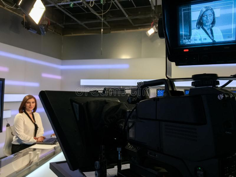 TV reporter at the news desk. TV reporter is live at the news desk presenting the news stock image