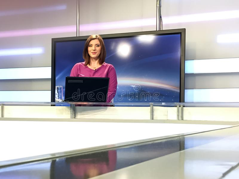 TV reporter at the news desk. TV reporter is live at the news desk presenting the news royalty free stock image
