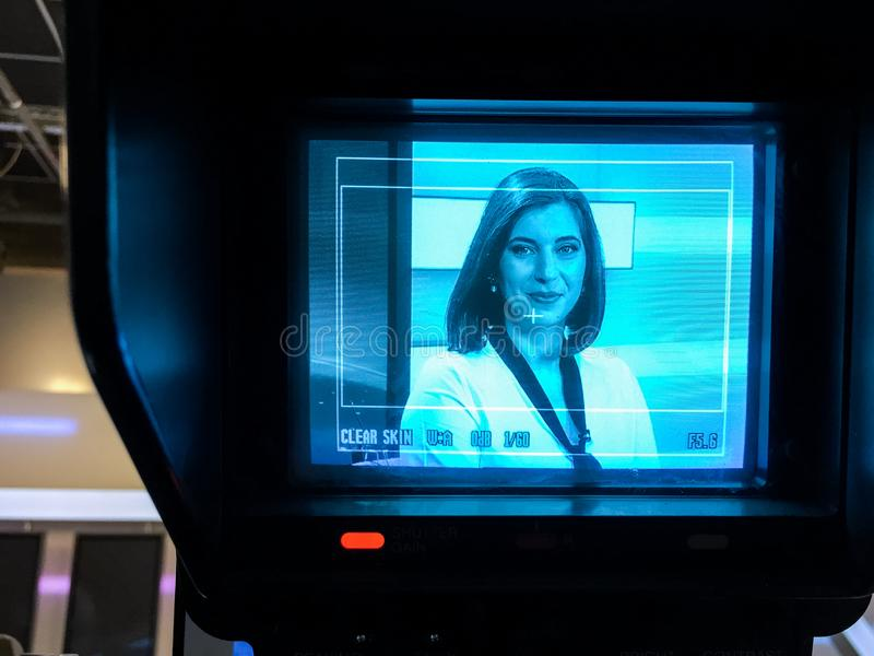 TV reporter at the news desk. Smiling TV reporter is live at the news desk presenting the news. Image seen on the TV set video camera screen stock images