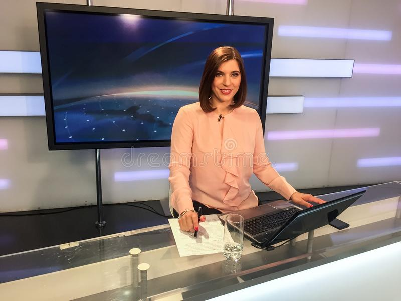 TV reporter at the news desk. TV reporter is live at the news desk presenting the news royalty free stock photography