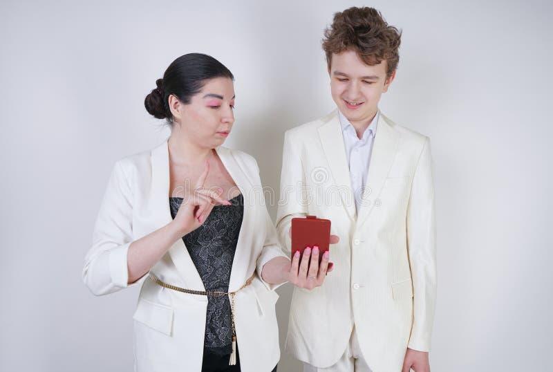 Tv? roliga v?nner som poserar med smartphonen, har gyckel och g?r selfie den vuxna flickan och ton?ringen tar sj?lvfoto p? vit ba fotografering för bildbyråer