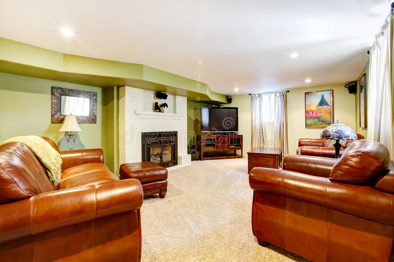 Tv room with green walls, leather sofas. And fireplace and beige carpet royalty free stock photography