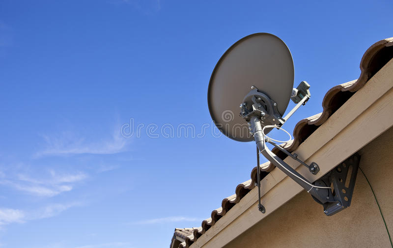 TV Satellite Dish. Mounted on a house stock photos