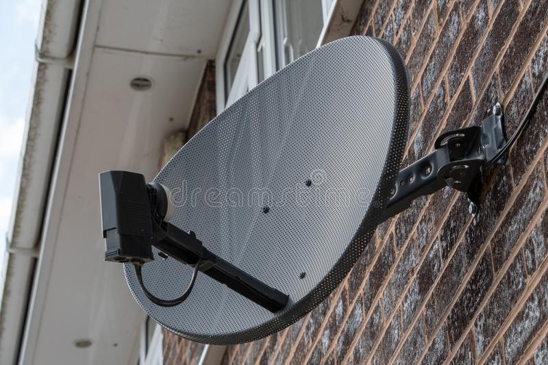 TV satellite dish on a brick wall. TV satellite dish mounted on a brick wall stock image