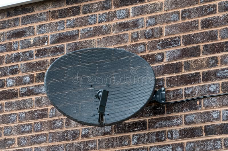 TV satellite dish on a brick wall. TV satellite dish mounted on a brick wall stock photo
