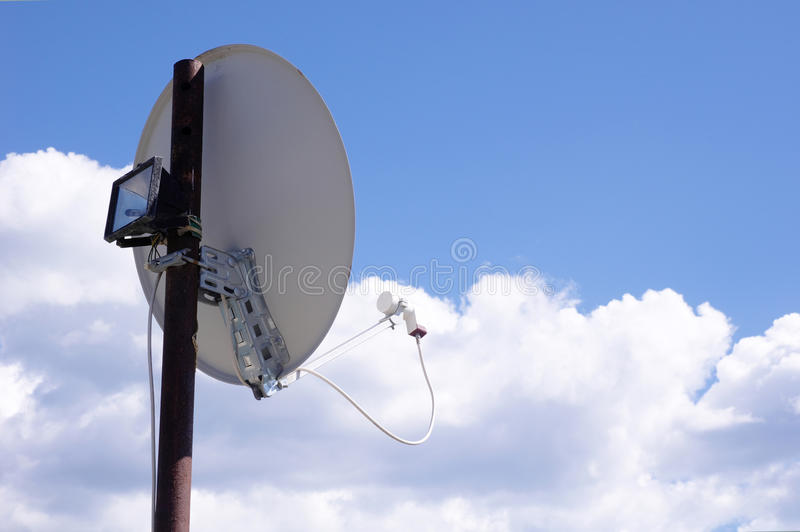 TV Satellite Dish mounted on a stake in sky. TV Satellite Dish mounted on a stake in cloudy sky royalty free stock image