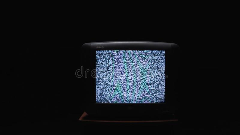 TV screen on at night with a white noise. Stock. Static noise on the old TV screen in the dark.  stock images