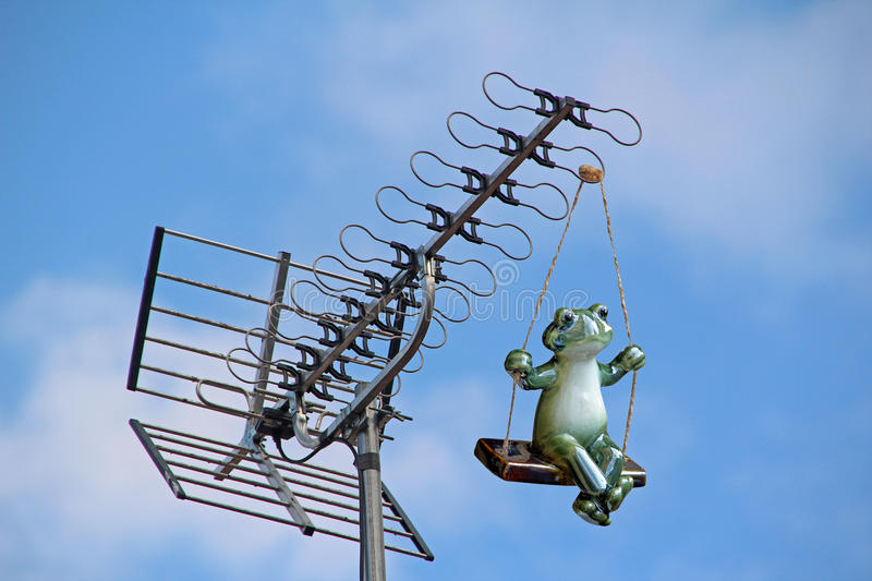 Tv signal interference frog. Conceptual photo of a frog swinging from a tv aerial causing signal interference! photo ideal for pest control,equipment malfunction stock photos