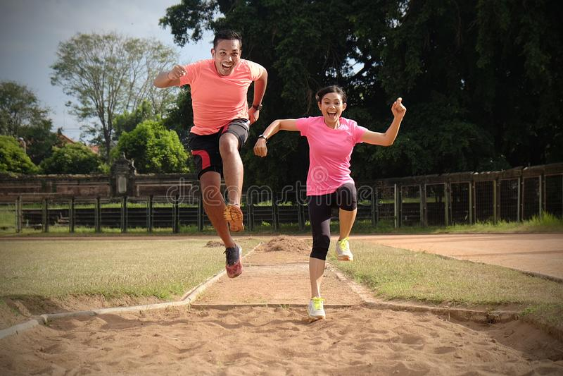 Tv? sportpartners joggar tillsammans p? en solig dag som b?r orange och rosa skjortor De ser de, och leendet, tycker om arkivfoto