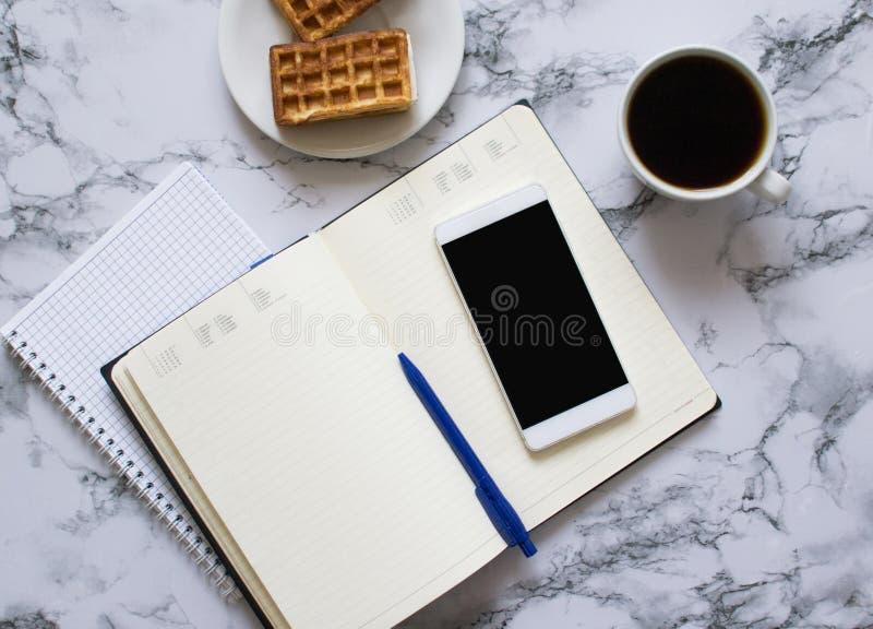 Tv? stadsplanerare marmorerar p? bakgrund, kaffe, dillandear och smartphonen royaltyfri fotografi