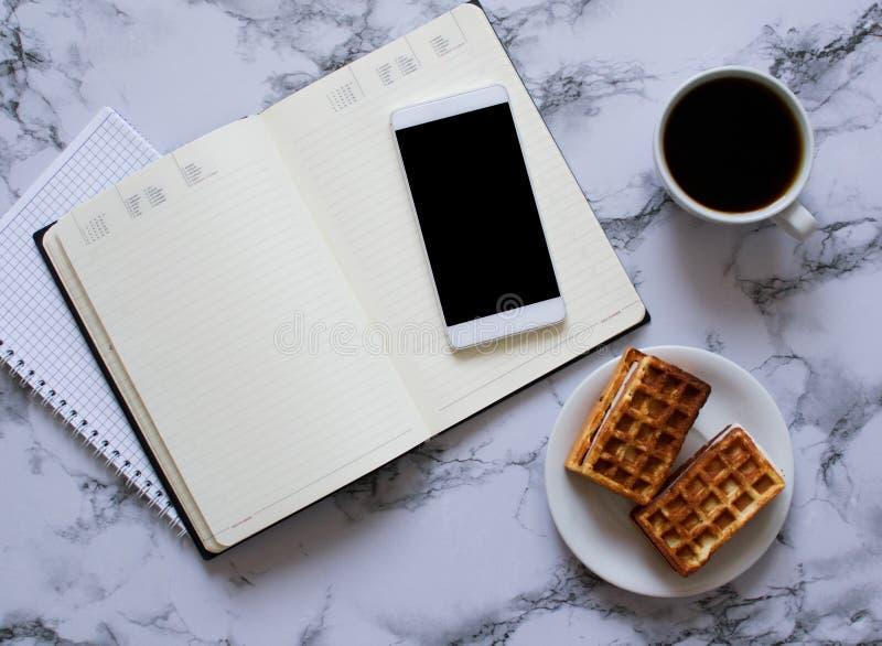 Tv? stadsplanerare marmorerar p? bakgrund, kaffe, dillandear och smartphonen arkivbild