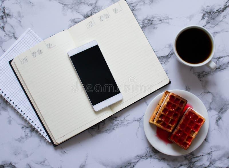 Tv? stadsplanerare marmorerar p? bakgrund, kaffe, dillandear och smartphonen royaltyfria foton