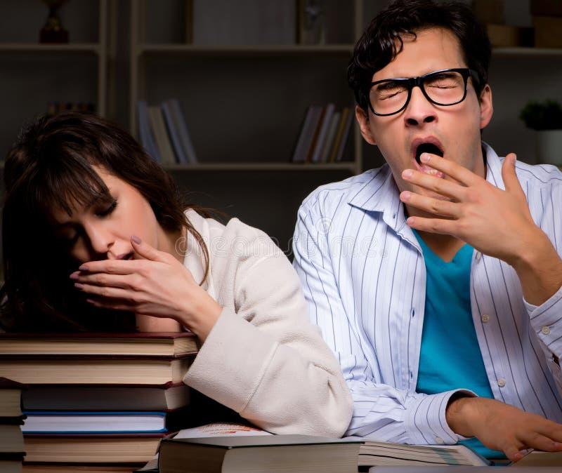 Tv? studenter som studerar sent att f?rbereda sig f?r examina royaltyfri bild