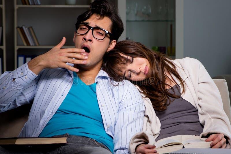 Tv? studenter som studerar sent att f?rbereda sig f?r examina arkivfoton