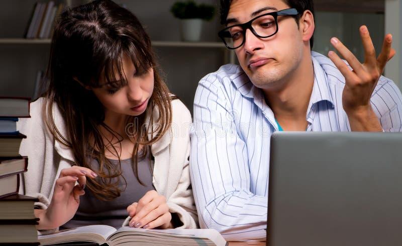 Tv? studenter som studerar sent att f?rbereda sig f?r examina royaltyfri fotografi