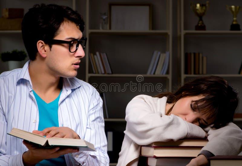 Tv? studenter som studerar sent att f?rbereda sig f?r examina royaltyfria foton