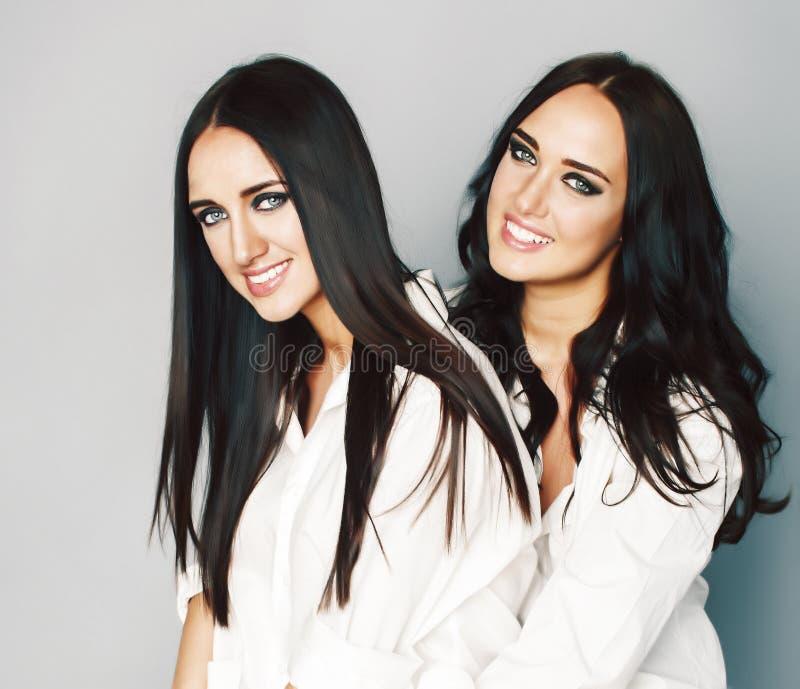 Tv? systrar kopplar samman att posera som g?r fotoselfie, kl?dde samma vit skjorta, olika frisyrv?nner, livsstilfolk arkivbilder
