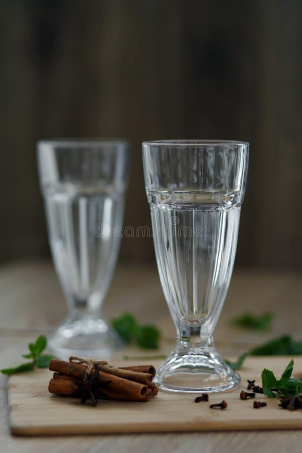 Tv? tomma exponeringsglas p? en tr?plattform med ingredienser f?r framst?llning av en varm vitamindrink royaltyfria foton