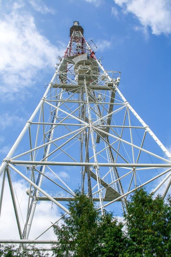 TV-toren op een achtergrond van blauwe hemel met wolken stock afbeeldingen