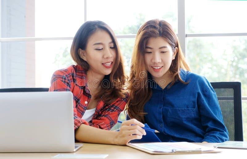 Tv? unga asiatiska kvinnor som arbetar med det hemmastadda kontoret f?r b?rbar datordator med det lyckliga sinnesr?relse?gonblick royaltyfria foton