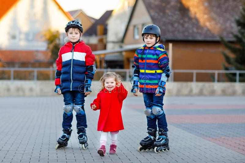 Tv? ungepojkar och liten litet barnflicka som tillsammans utomhus spelar p? solig dag Br?der i skyddss?kerhetskl?der arkivfoto