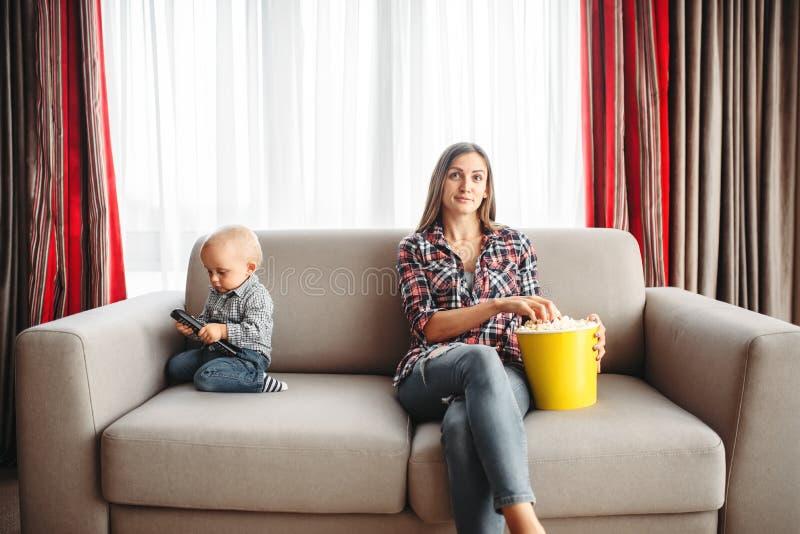 TV van het moederhorloge, weinig mannelijk jong geitje speelt dichtbij stock fotografie