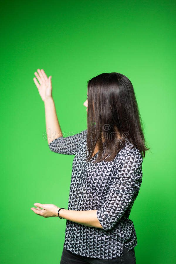 TV weather news reporter at work.News anchor presenting the world weather report.Television presenter recording in a green screen. Studio.Young woman with copy royalty free stock image