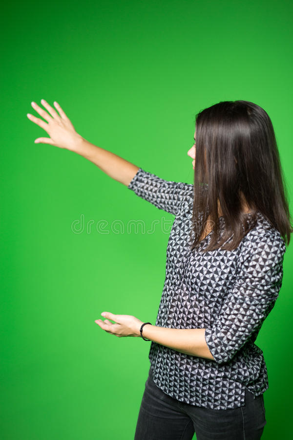 TV weather news reporter at work.News anchor presenting the world weather report.Television presenter recording in a green screen. Studio.Young woman with copy stock images