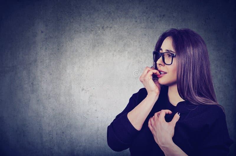 Tveksam angelägen kvinna som biter hennes fingernaglar som ser sideway royaltyfria foton