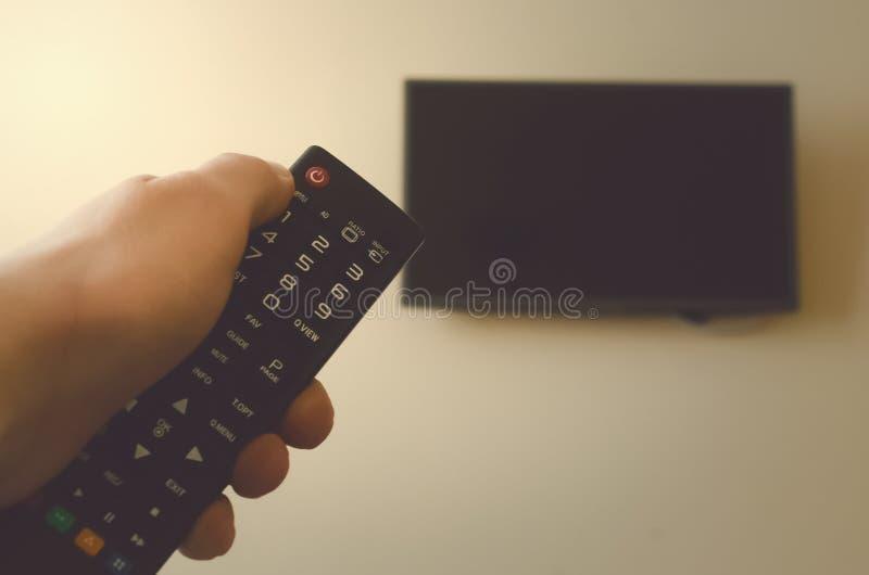 TVfjärrkontroll i manliga händer arkivbilder