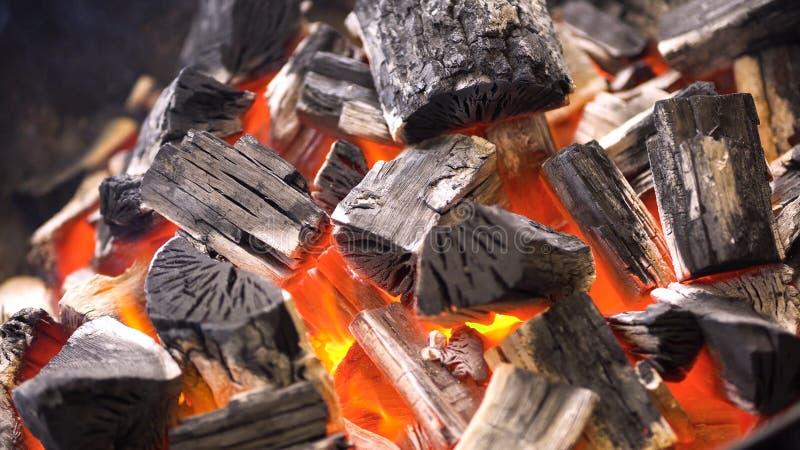TView av varma flammande kolbriketter som glöder i bbq-gallergropen Brännande kol för att laga mat grillfestmat close upp royaltyfri bild