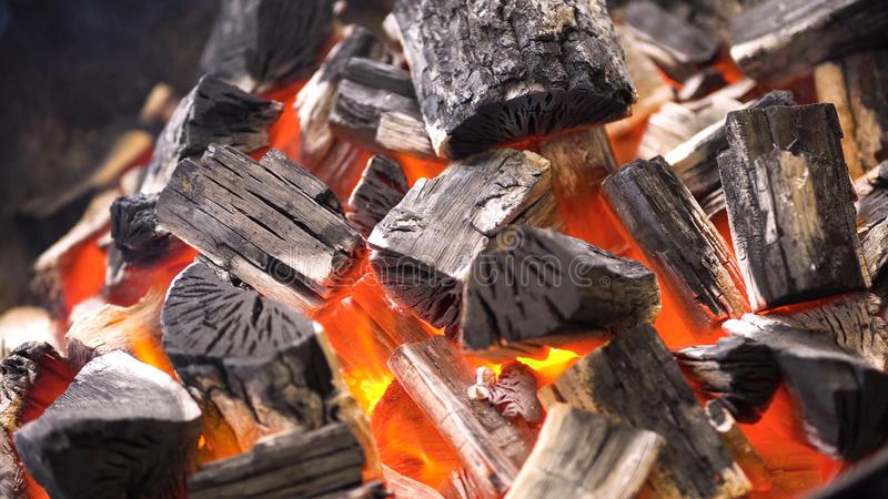 TView Of Hot Flaming Charcoal Briquettes Glowing In The BBQ Grill Pit. Burning Coals For Cooking Barbecue Food. Close Up royalty free stock image