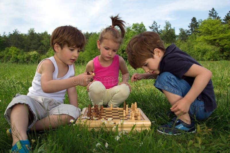 Tvilling- bröder som spelar schack i parkera medan gullig liten flicka som håller ögonen på The Game royaltyfri bild