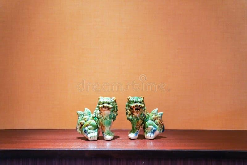 Tvilling- grön seramic lejonställning i mitt av ramen med volframljus arkivbilder