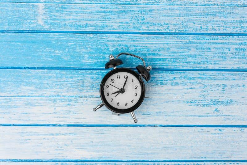 Tvilling- Klocka liten ringklocka på blått och vitt trä för hög kontrast fotografering för bildbyråer
