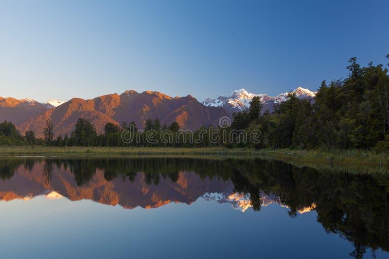 Tvilling- maxima reflekterar i den härliga sjön Matheson på solnedgången som är ny royaltyfria bilder
