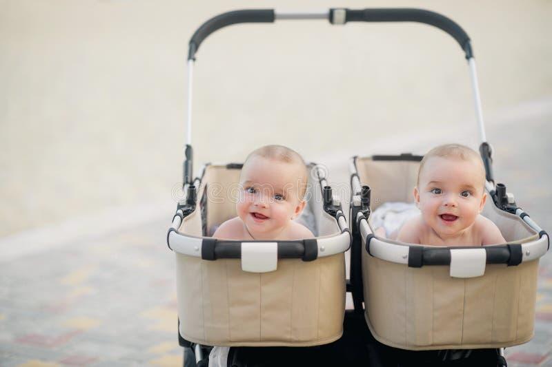 Tvilling- pojkar ser ut ur sittvagnen royaltyfri fotografi