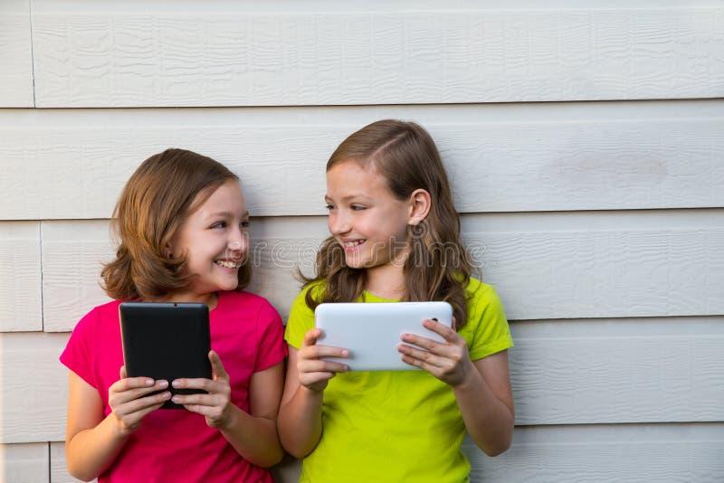 Tvilling- systerflickor som spelar med minnestavlaPC:n som är lycklig på den vita väggen arkivfoton