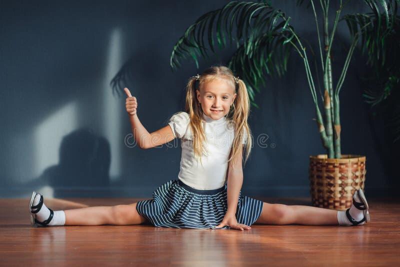 Tvinnar den härliga flickan för ung kondition som gör sportövning och att sitta på splittringar, på yoga som är matt i morgon Sun royaltyfri bild