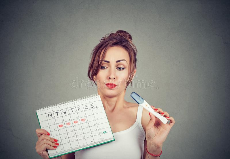 Tvivel kvinna som håller ett positivt graviditetstest och sin menstruationskalender royaltyfria bilder