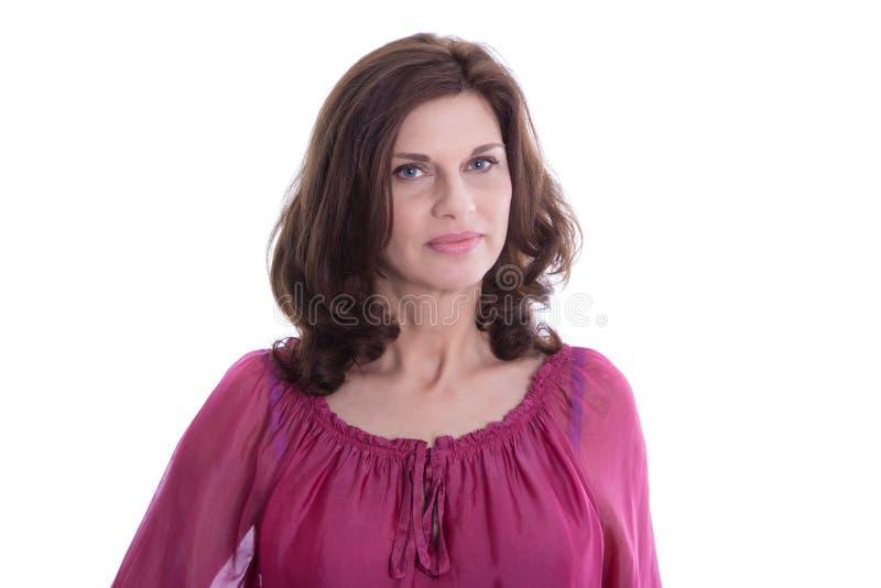 Tvivelaktigt äldre isolerad kvinna i femtiotalet i rosa skjorta royaltyfri bild