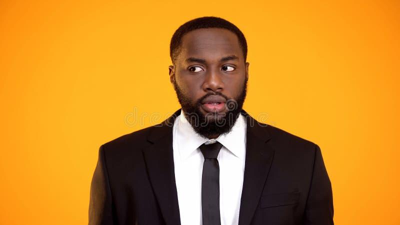 Tvivelaktigt afro--amerikan man i formalwearen som suspiciously ?t sidan ser os?kerhet fotografering för bildbyråer