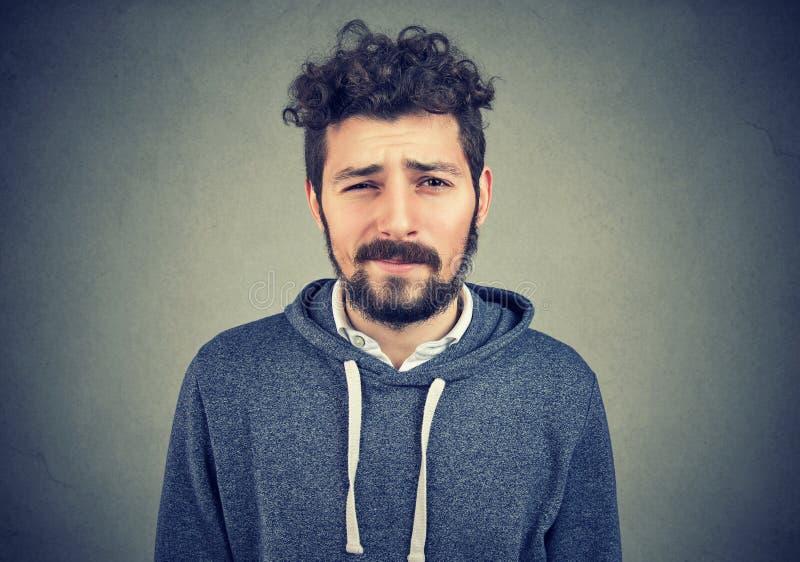Tvivelaktigt ung hipsterman som ser kameran fotografering för bildbyråer