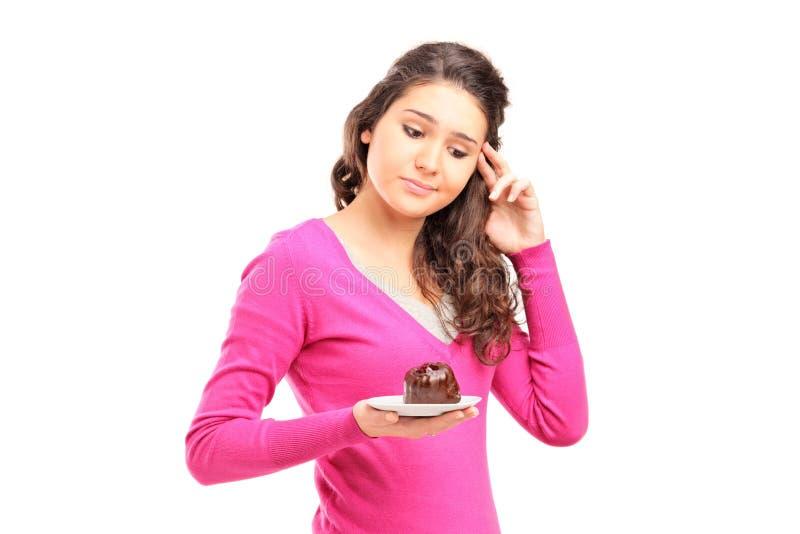 Tvivelaktigtt kvinna som rymmer en cake i henne hand arkivbild