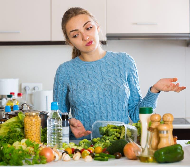 Tvivla flickan som tänker vad för att laga mat för matställe royaltyfria bilder