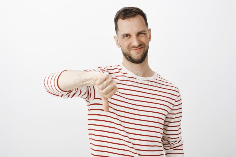 Twój pomysł ssa Portret grimacing od niechęci i pokazuje kciuki nieporuszony nierad przystojny mężczyzna z brodą, zdjęcie stock