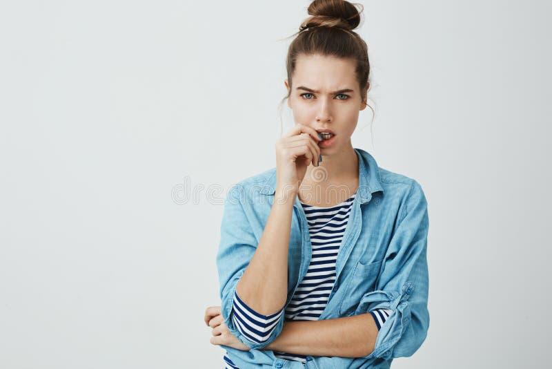 Twój słowa no dopasowywają prawdy Portret marszczy brwi kciuk i gryźć atrakcyjna młoda kobieta z babeczki fryzurą, podczas gdy zdjęcie stock